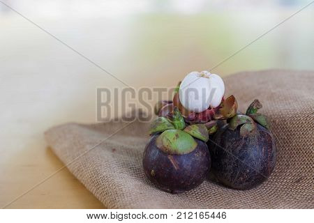 Mangosteen and cross section showing the thick purple skin and white flesh of the queen of friuts Delicious mangosteen fruit arranged on sackcloth