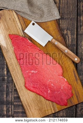 Fresh raw beef steak in black on kitchen wooden board with hatchet knifeisolated on white background