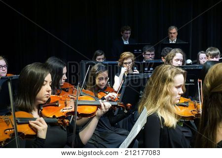 JOLIET, ILLINOIS / UNITED STATES - MARCH 20, 2016: Violinists of the Metropolitan Youth Symphony Orchestra (MYSO) perform music in a concert in the Fine Arts Theater of Joliet Junior College.
