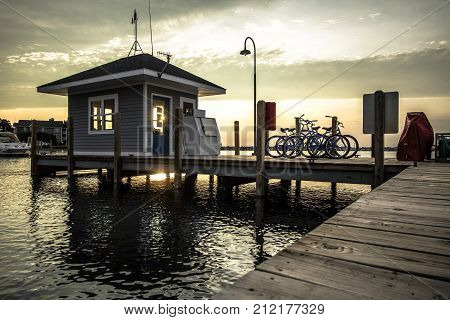 Seaside Summer Sunset Background.  Long wooden dock with small building and row of bicycles at sunset on the Lake Michigan coast.