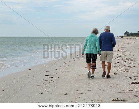 Senior Couple Walking on Beach Sanibel Florida