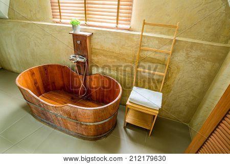 Wooden bathtub in the bathroom loft style