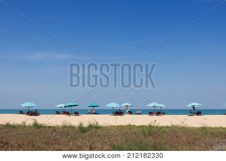 Chairs and umbrella on tropical beach .