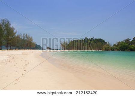 Tropical white sand beach with emerald sea.