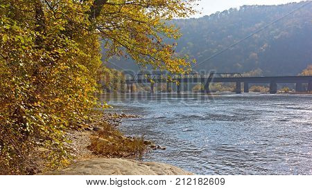 Golden autumn on Potomac River near Harpers Ferry historic town. Railroad bridge mountains and river banks in fall West Virginia USA.