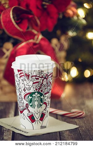 Dallas TX - November 4 2017: Starbucks popular holiday beverage served in the new 2017 designed holiday cup. Displayed with candy cane on wooden rustic table. Sparkling Christmas tree lights background.