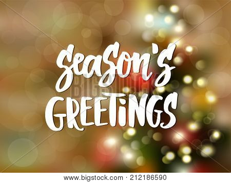 Season's greetings text, hand drawn lettering. Blurred background with Christmas tree and glowing lights. Holiday greetings quote. Great for Christmas, New year cards, posters, gift tags. Vector.