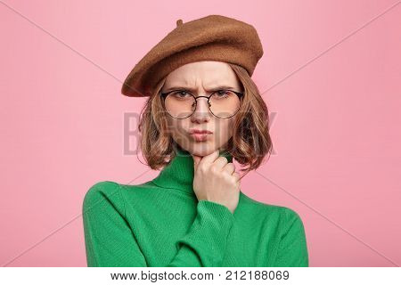 Portrait of sullen angry offended pretty girl frowns face pouts lips being irritated and resentful isolated over pink background. Discontent young woman with gloomy expression after quarrel poster