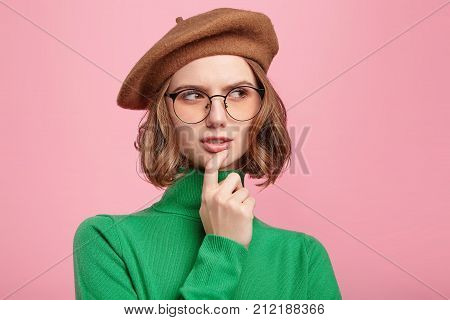 Indoor Shot Of Pensive Young Female Teacher In Green Polo Neck Sweater, Beret And Round Spectacles L