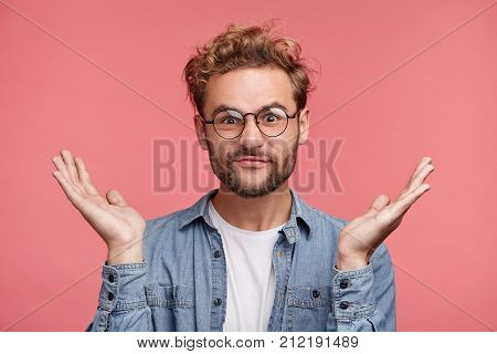 Bearded Caucasian Male Has Hesitatnt And Displeased Expression, Gestures Doubtfully, Has No Answer O