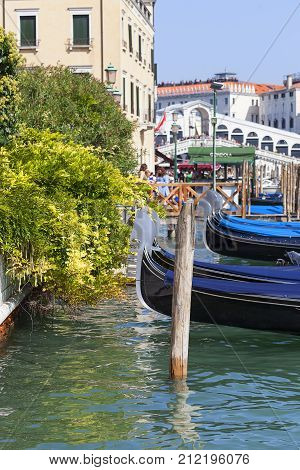 VENICE ITALY-SEPTEMBER 22 2017: View on Grand Canal with gondolas in the harbor and Rialto Bridge (Ponte de Rialto) . It's one of the four bridges over the canal