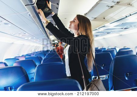 Female student putting her hand luggage into overhead locker on airplane.