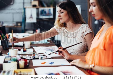 Two adult female students working on their paintings studying at art school.
