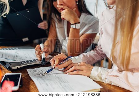 Close-up view of young women working on accounting paperwork checking and pointing at documents sitting at desk in office.