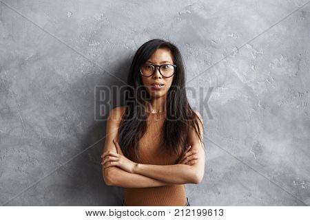 Horizontal portrait of indignant annoyed young Chinese woman wearing trendy eyeglasses and sleeveless top holding arms folded as sign of protest indignation dislike or disapproval. Body language