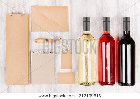 Corporate identity template for wine industry blank brown kraft packaging stationery merchandise set with bottles different wine on soft white wood background. Mock up for branding advertising design business presentations and portfolios.