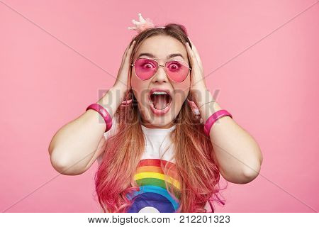 Stupefied Shocked Fashionable Female Wears Pink Sunglasses, Stares At Camera, Keeps Hands On Head, F