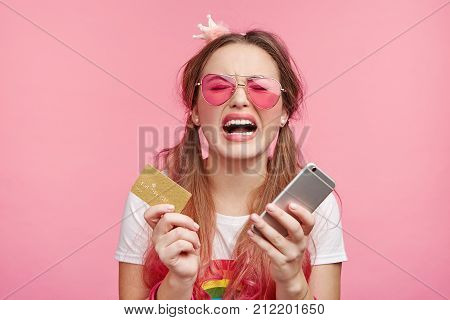 Stressful Coquette Female In Panic Keeps Modern Smart Phone And Credit Card, Forgets Password, Can`t
