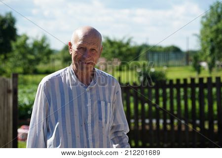 Portrait of mature smiling man farmer dressed in shirt in the background of growing trees in the garden in sunny summer day. Farmer is charged energy of nature