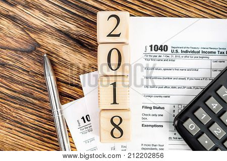 Pay tax in 2018 year concept. Numbers 2018 wit tax form 1040 calculator and pen on the table. Top view.