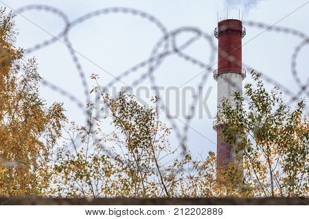 A Pipe With Smoke Behind A Fence With Barbed Wire.