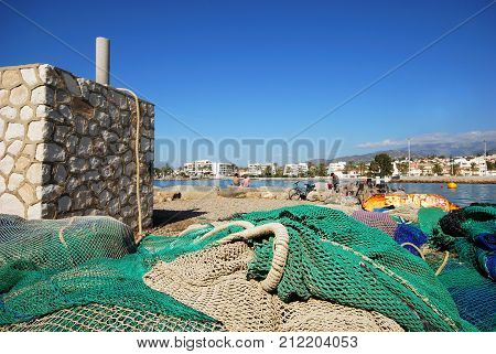CALETA DE VELEZ, SPAIN - OCTOBER 27, 2008 - Fishing nets on quayside with couple sitting on harbour edge looking out to sea Caleta de Velez Malaga Province Andalusia Spain Western Europe, October 27, 2008.
