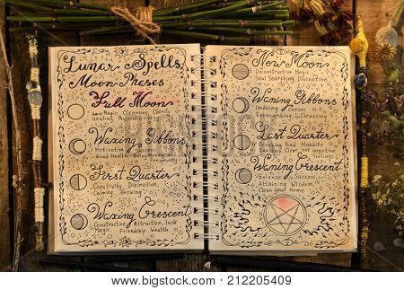 Open witch book with lunar spells and magic wands in candle light. Occult, esoteric, divination and wicca concept. Halloween vintage background