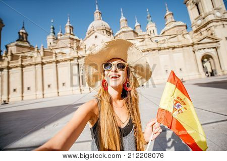 Young woman tourist standing with spanish flag in front of the famous cathedral on the central square during the sunny weather in Zaragoza city, Spain
