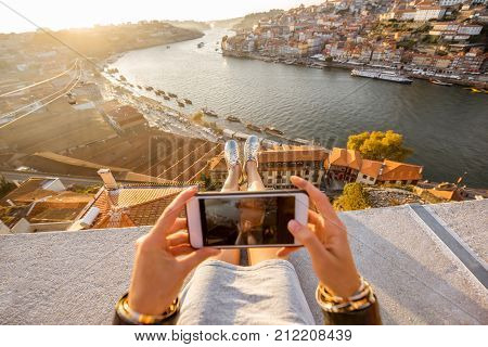 Woman photographing with phone beautiful landscape view on Porto city during the sunset in Portugal