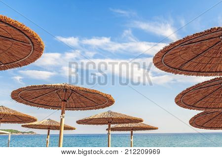 Straw sunshade and a beautiful beach inviting to relax