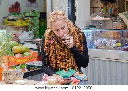 JERUSALEM ISRAEL - NOVEMBER 3 2014: Undefined young woman smock and read messages on mobile phone at Mahane Yehuda Market Jerusalem Israel