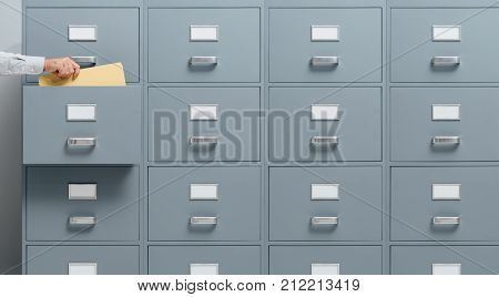 Office worker taking a file from a filing cabinet drawer business and administration concept