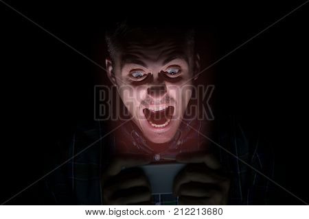 The Guy In The Shirt Sits In The Dark And Looks At The Mobile Phone. On The Face Is The Emotion Of F