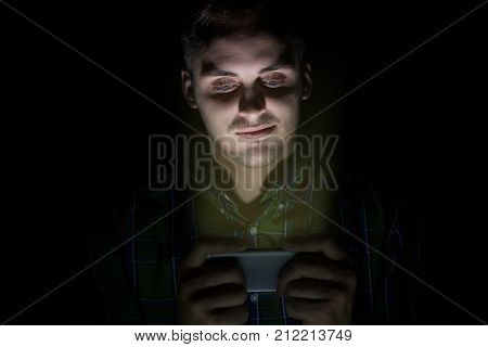 The Guy In The Shirt Sits In The Dark And Looks At The Mobile Phone. On The Face Is The Emotion Of E