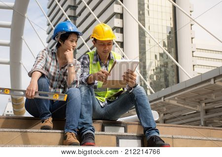 Two construction engineers working outdoors,discussing the construction in construction site with documents