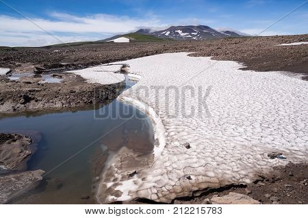 View of the snowfields and the volcano Gorely in the background. Kamchatka peninsula summer. Russia.