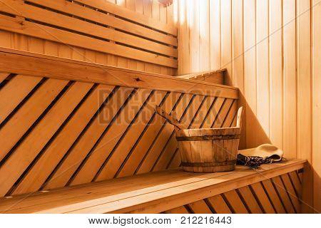 wooden sauna cabin with sauna accessories, bucket, broom, oak scoop