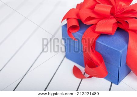 Blue gift box with red ribbon and bow on wooden background