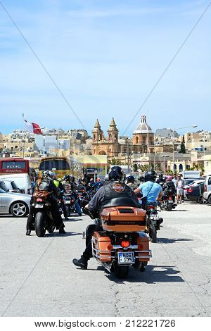 MARSAXLOKK, MALTA - APRIL 1, 2017 - Group of motor cyclists parking with the parish church of Our Lady of Pompei to the rear Marsaxlokk Malta Europe, April 1, 2017.