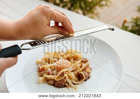 Chef grating parmesan cheese on traditional italian pasta carbonara with bacon and egg yolk. Traditional italian cuisine dish. Restaurant food closeup. Shallow DOF, selective focus