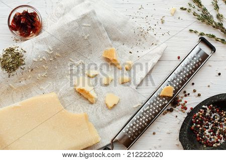 Parmesan top view with small grater, various herbs and seasoning, rosemary and pepper. Classic italian cuisine cooking ingredients, grated hard cheese, top view