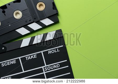 movie clapper and video cassette tapes on green background; film cinema and video photography concept