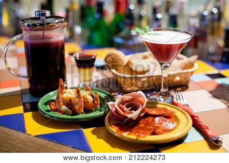 Booze party tapas bar still life scene. Beautiful cocktails, shot and long drinks, cold starters marinated shrimp jamon parma chorizo sausages and baguette on clay plates. Selective focus photography.