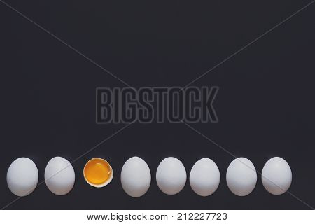 White home eggs arranged in a row with one cracked, showing yolk on black background