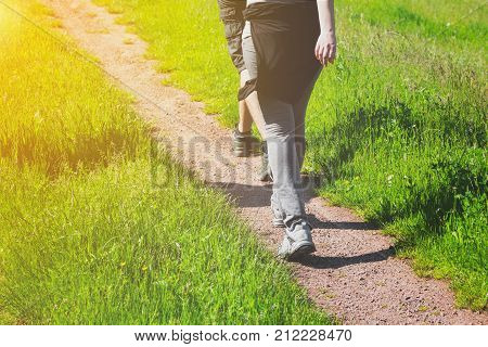Young people walking away from the camera along a rural track as they enjoy a sunny spring day hiking in nature through lush green grass with the glow of the sun in the corner