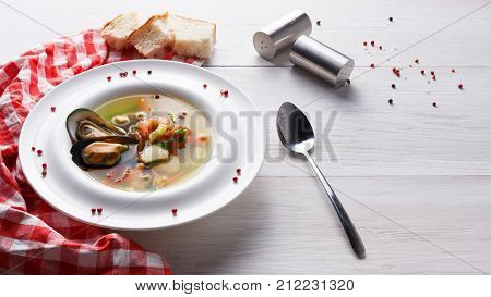 French cuisine restaurant. Seafood soup with white fish, shrimps and mussels in plate sprinkled with spices. Fresh exclusive meals on white wooden table with checkered cloth and cutlery, copy space