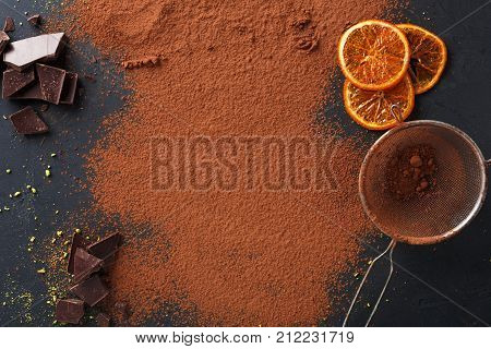 Sweet background. Cocoa powder in a sieve and sprinkled on surface, orange citrons and chocolate pieces on black slate. Top view, copy space poster