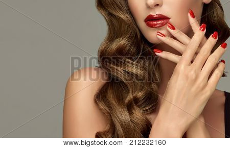 Beautiful girl showing red  manicure nails . makeup and cosmetics. Brunette  girl with long  and   shiny curly hair