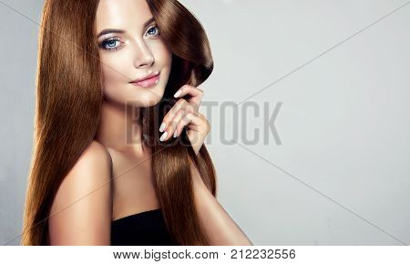 Young, brown haired woman  with voluminous hair.Beautiful model with long, dense, straight hairstyle and vivid makeup, is touching own hair with tenderness. Symbol of attentiveness to hair and good care of it. Perfect hair  and sexy look.Incredibly dense,