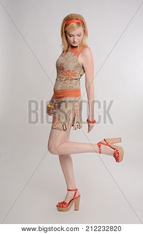Beautiful girl posing on gray background, playful pose. Warm colors, an orange hoop put on your head, clothes from the 1970s. She is dressed in a dress with orange accents. Bright bracelets on the hands.